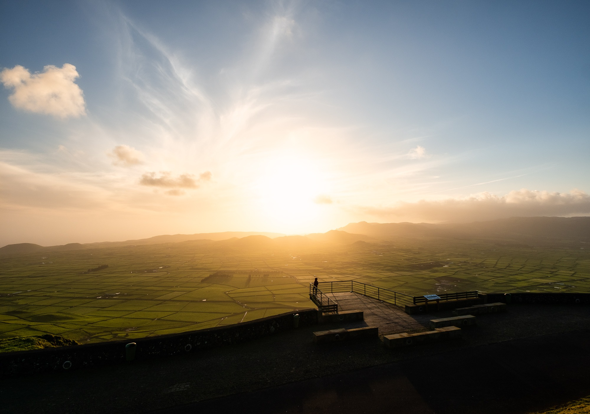 Silhouette of a girl enjoying the view at sunset in Serra do Cume viewpoint, Terceira Island, Azores